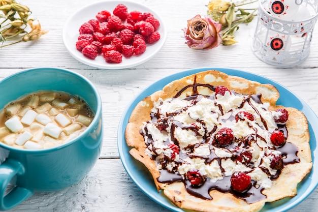 Hausgemachte pfannkuchen oder russische pfannkuchen mit schokoladensauce, schlagsahne und himbeeren