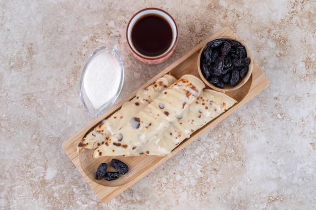 Hausgemachte pfannkuchen rollen mit rosinen und kondensmilch