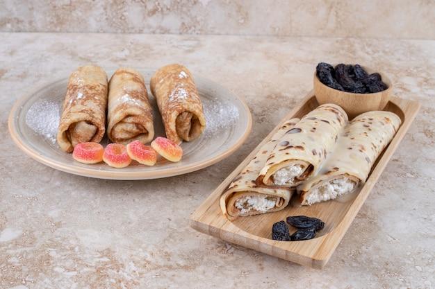 Hausgemachte pfannkuchen rollen mit rosinen und zuckerpulver