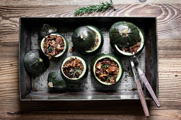 Hausgemachte pfifferlinge gefüllt runde zucchini auf holztisch