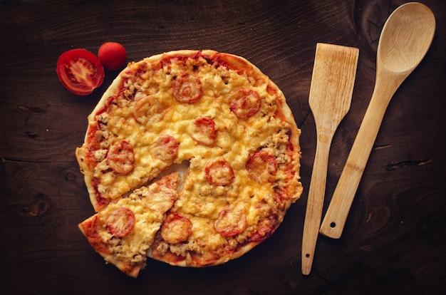 Hausgemachte pikante pizza. pizza mit scheibenschnitt.
