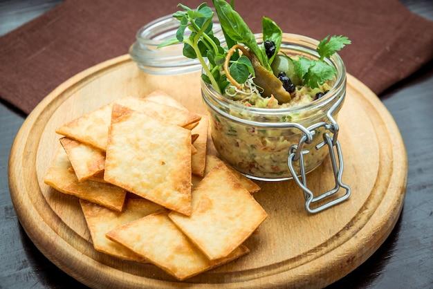 Hausgemachte pilz-bohnen-paste. pastete im glas auf rustikalem holztisch. nützliches und gesundes vegetarisches essen