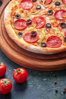 Hausgemachte pizza auf holzbrett und tomaten auf isolierter dunkler oberfläche
