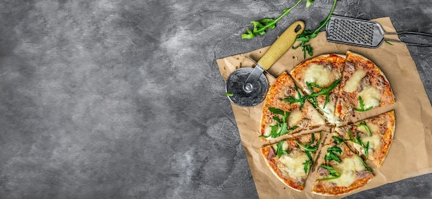 Hausgemachte pizza aus thunfisch, mozzarella, parmesan und rucola. draufsicht.