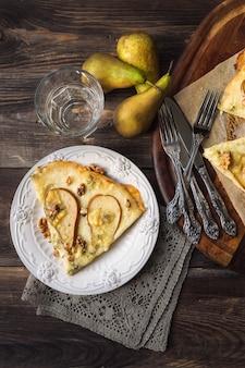 Hausgemachte pizza mit birne, blauschimmelkäse, mozzarella und wallnüssen auf rustikaler holzoberfläche. draufsicht.