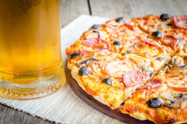 Hausgemachte pizza mit einem glas bier