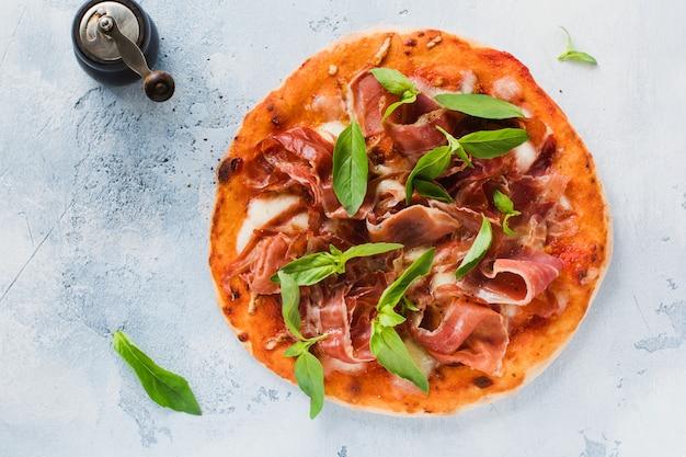 Hausgemachte pizza mit jamon, mozzarella und basilikumblättern auf altem betonhintergrund. draufsicht.