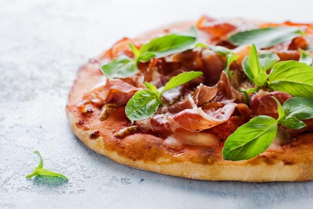 Hausgemachte pizza mit jamon, mozzarella und basilikumblättern auf altem betonhintergrund. selektiver fokus