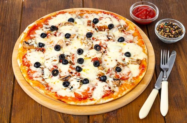 Hausgemachte pizza mit peperoni, pilzen, mozzarella und oliven.