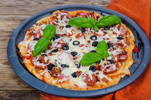 Hausgemachte pizza mit salami, mozzarella und oliven.