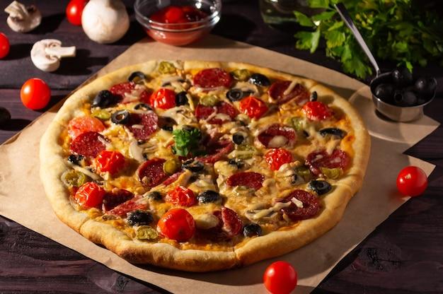 Hausgemachte pizza mit salami, pilzen und kirschtomaten auf dunklem hintergrund. seitenansicht.