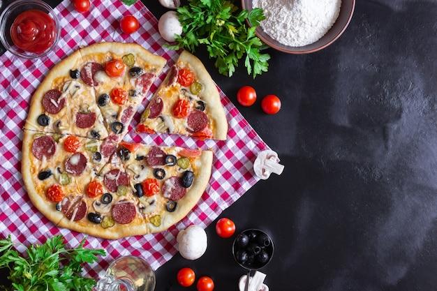 Hausgemachte pizza mit salami, pilzen und kirschtomaten auf schwarzem hintergrund. ein rot kariertes handtuch. freier platz für text, ansicht von oben.