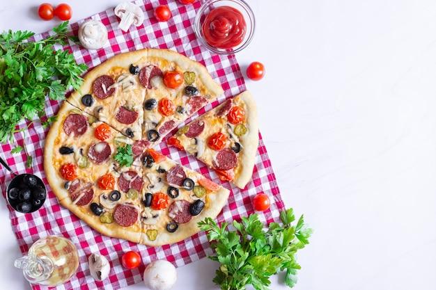 Hausgemachte pizza mit salami, pilzen und kirschtomaten auf weißem hintergrund. ein rot kariertes handtuch. freier platz für text, ansicht von oben.