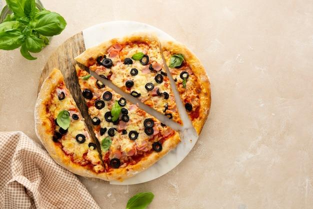 Hausgemachte pizza mit schinken, schwarzen oliven, käse und frischem basilikum auf marmorplatte draufsicht top