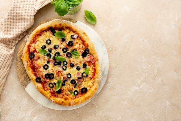 Hausgemachte pizza mit schinken, schwarzen oliven, käse und frischem basilikum draufsicht