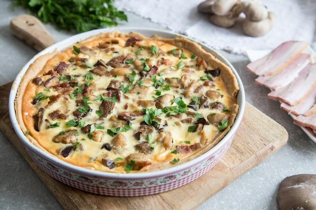Hausgemachte quiche lorraine mit hühnchen, champignons, käse und speck. tarte mit hühnchen hühnerpastete. pilz-kuchen
