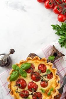 Hausgemachte quiche-torte mit kirschtomaten, basilikum, gewürzen und käse auf weißem steinhintergrund. selektiver fokus