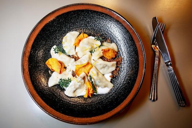 Hausgemachte ravioli, knödel, in einem teller auf einem schwarzen