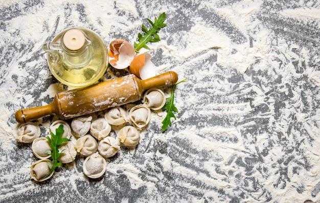Hausgemachte ravioli mit olivenöl und nudelholz. auf dem steintisch mit mehl. freier platz für text. draufsicht