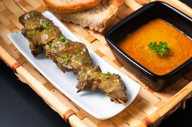 Hausgemachte rindfleisch satay gegrillte und würzige erdnussgewürzsauce des asiatischen lebensmittelkonzepts auf bambustablett mit kopienraum
