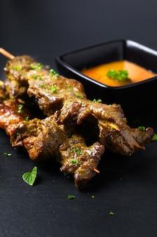 Hausgemachte rindfleisch satay gegrillte und würzige erdnussgewürzsauce des asiatischen lebensmittelkonzepts auf schwarzem schieferbrett mit kopienraum