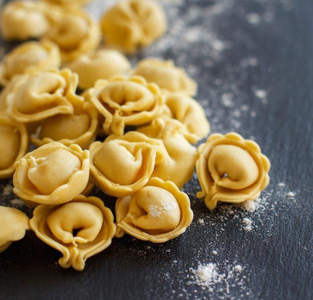 Hausgemachte rohe italienische tortellini auf einem dunklen