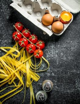 Hausgemachte rohe nudeln mit tomaten auf einem ast, eiern und gewürzen. auf schwarzem rustikalem hintergrund