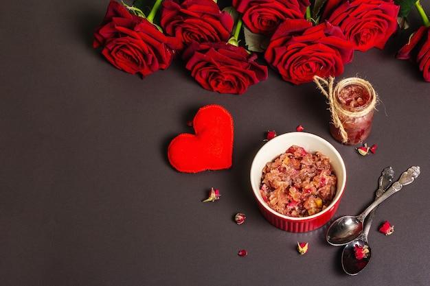 Hausgemachte rosenblütenmarmelade. süßes frühstück für liebhaber, strauß frischer rosen, festliche einrichtung. valentinstag, hochzeit oder geburtstagskonzept, schwarzer steinbetonhintergrund