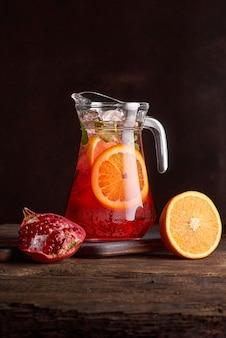 Hausgemachte rotwein-sangria mit orange, granatapfel und eis in glas und krug auf rustikalem holzhintergrund. kopieren sie platz, selektiver fokus. gesundes essen. foto für die speisekarte