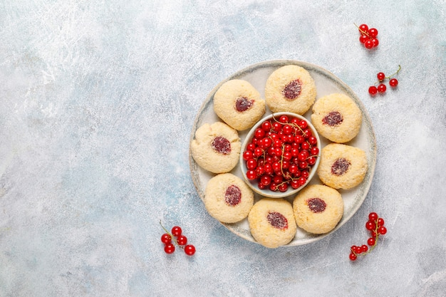 Hausgemachte rustikale marmelade der roten johannisbeere, die kekse mit kokosnuss füllt