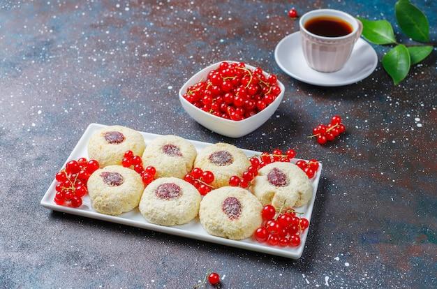 Hausgemachte rustikale marmelade der roten johannisbeere, die kekse mit kokosnuss und tasse tee füllt