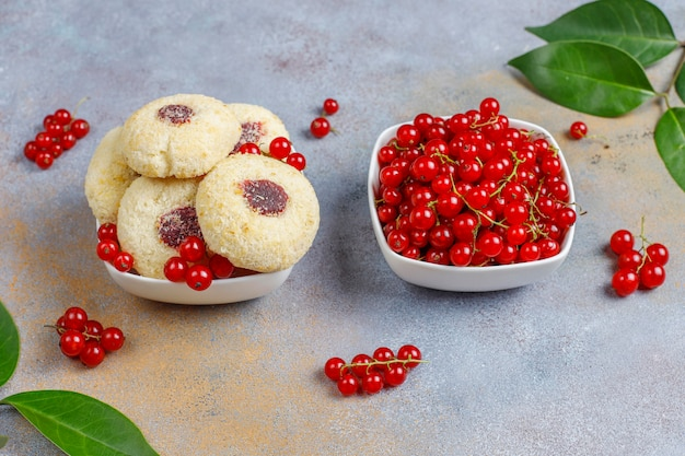 Hausgemachte rustikale marmelade mit roten johannisbeeren, die kekse mit kokosnuss- und johannisbeerbeeren füllt