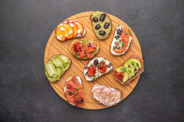 Hausgemachte sandwiches mit brot und verschiedenen zutaten und gewürzen auf hellem raum. gesundes leckeres essen zum frühstück und mittagessen