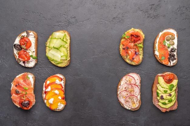 Hausgemachte sandwiches mit brot und verschiedenen zutaten und gewürzen in einem dunklen raum. gesundes leckeres essen zum frühstück und mittagessen