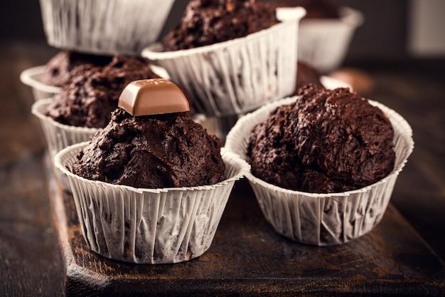 Hausgemachte schokoladen-bananen-muffins auf dunklem holztisch. süße minikuchen. party essen oberfläche