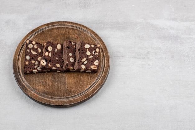 Hausgemachte schokoladen-brownies auf einem holzteller auf dem marmortisch.