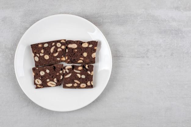 Hausgemachte schokoladen-brownies auf einem teller, auf dem marmortisch.