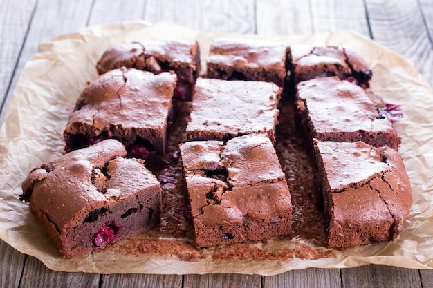 Hausgemachte schokoladen-brownies mit kirsche auf backpapier und hölzernem hintergrund