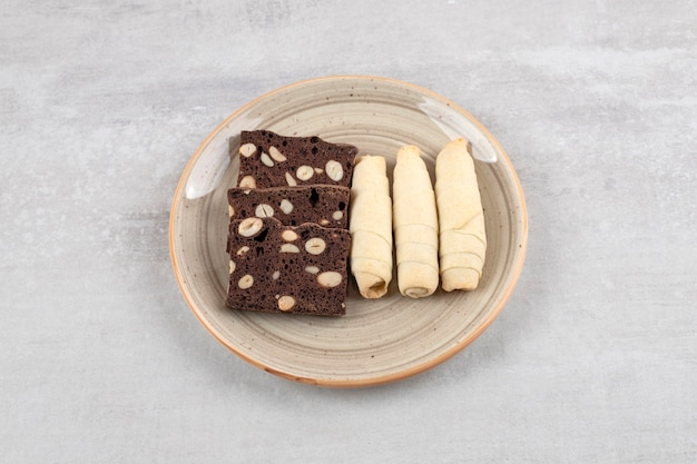 Hausgemachte schokoladen-brownies und brötchen auf einem teller, auf dem marmortisch.