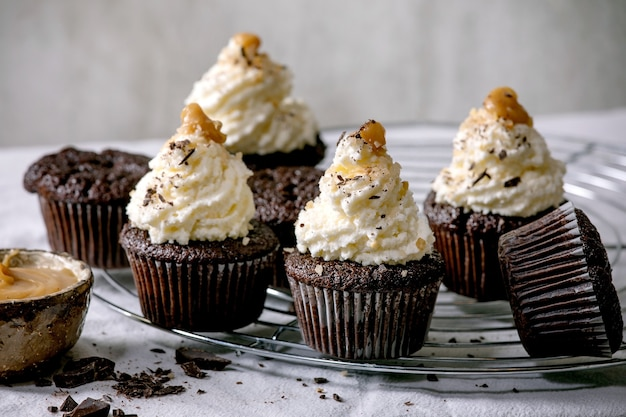 Hausgemachte schokoladen-cupcakes-muffins mit weißer buttercreme und gesalzenem karamell, serviert mit gehackter dunkler schokolade auf einem kühlregal auf einem weißen tischtuch.