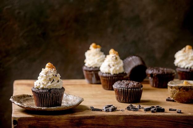 Hausgemachte schokoladen-cupcakes-muffins mit weißer schlagsahne-buttercreme und gesalzenem karamell auf keramikplatte, serviert mit gehackter dunkler schokolade auf holztisch. speicherplatz kopieren