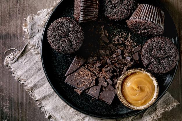 Hausgemachte schokoladencupcakes-muffins mit gesalzener karamellsauce und gehackter dunkler schokolade auf schwarzer keramikplatte über betonbeschaffenheitstabelle. flach liegen