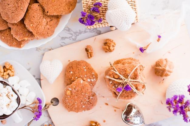 Hausgemachte schokoladenkekse mit walnüssen auf dem küchenbrett. tischdekoration zum frühstück. draufsicht