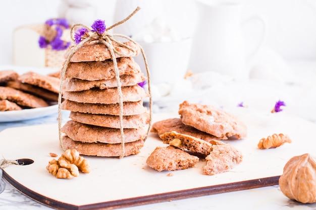 Hausgemachte schokoladenkekse mit walnüssen auf dem küchenbrett. tischdekoration zum frühstück