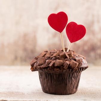 Hausgemachte schokoladenmuffins mit herz, weinlesehintergrund.