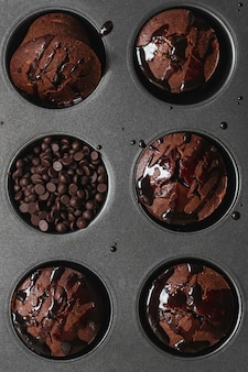 Hausgemachte schokoladenmuffins mit schokoladentropfen und sause