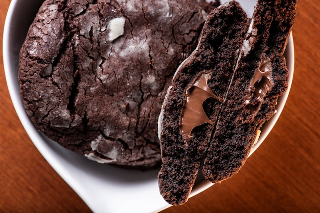 Hausgemachte schokoladenplätzchen gefüllt mit haselnusscreme. sie werden in zwei hälften geschnitten, um das innere zu sehen