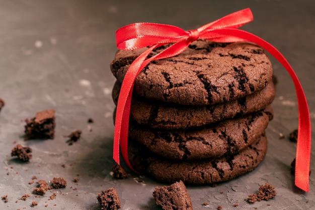 Hausgemachte schokoladenplätzchen mit rissen auf schwarzem hintergrund.