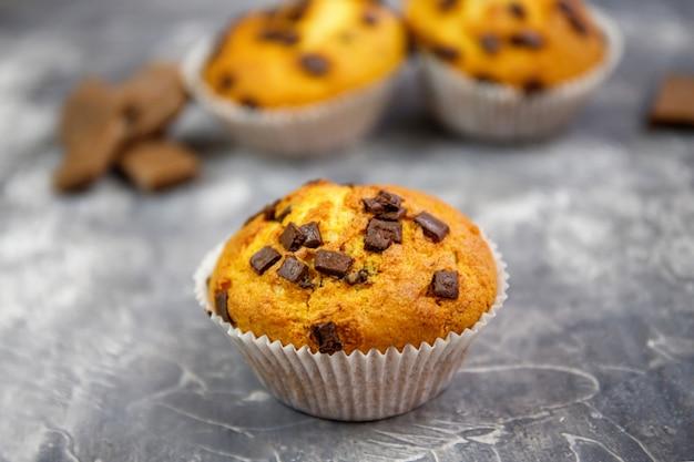 Hausgemachte schokoladensplitter-muffins auf rustikalem hintergrund