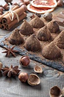 Hausgemachte schokoladentrüffel mit kakaopulver und sortierter schokolade mit nüssen und anderen gewürzen auf rustikalem alten küchentisch bestreut.